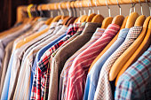 A group of striped, plain and checked shirts in a variety of colours, on wooden hangers.