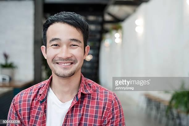 Lässige junge asiatische Geschäftsmann lächelnd in die Kamera, Porträt