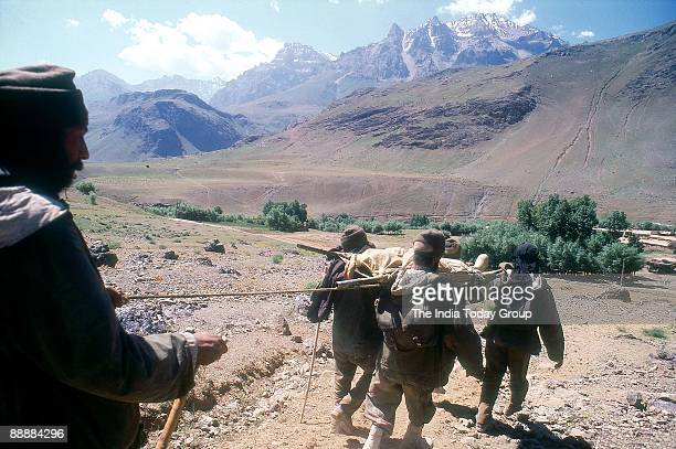 Casualities on stretchers are evacuated from hilly areas by Army personnel in Kargil conflict