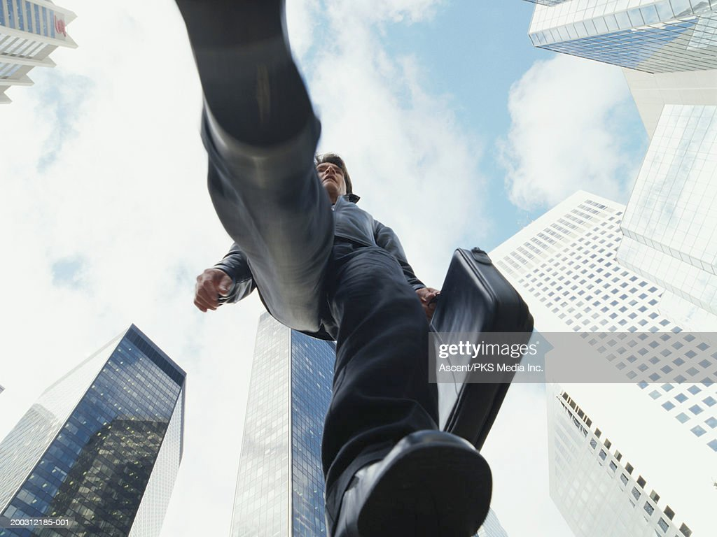 Casually dressed mature businessman walking in city, view from below : Stock Photo