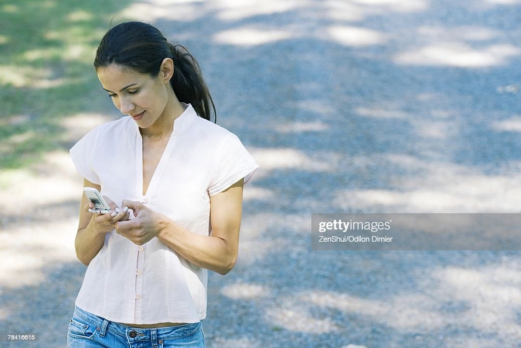 Casually dressed woman holding cell phone : Stock Photo