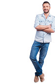 Full length of handsome young man in casual wear leaning at copy space and smiling while standing against white background