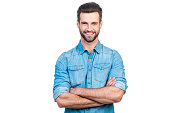 Confident young handsome man in jeans shirt keeping arms crossed and smiling while standing against white background