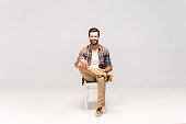 Studio shot of handsome young man sitting on the chair and looking at camera with smile