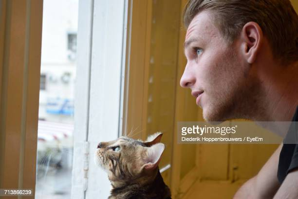 Cat And Man Looking Through Window