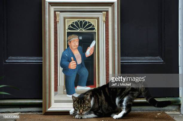 A cat examines an iconic painting by artist Beryl Cook outside Lyon Turnbull auctioneers on April 11 2013 in Edinburgh Scotland The painting of Rab C...