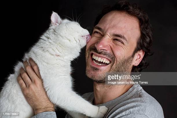 Cat licking man's face
