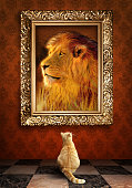 Cat looking at a portrait of lion in golden frame.