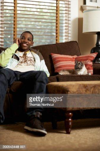 Cat lying beside teenage boy (14-16) talking on cell phone on sofa : Stock Photo