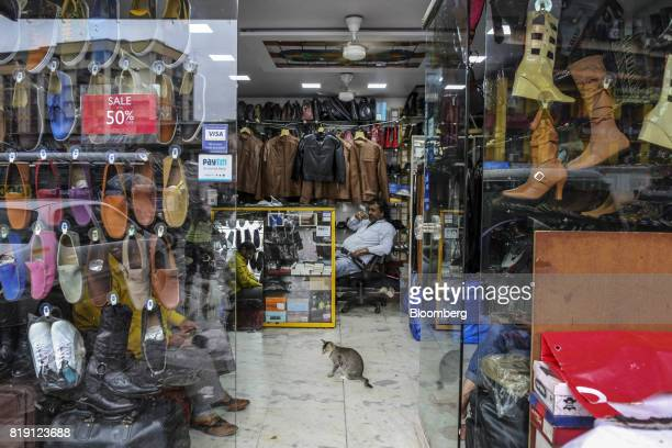 A cat sits as vendors wait for customers at a leather goods store in the Dharavi area of Mumbai India on Tuesday July 18 2017 India's new goods and...