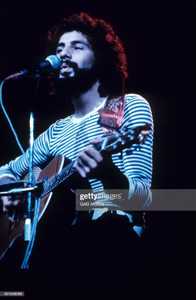 Cat Stevens performs on stage, circa 1975.