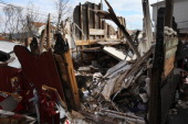 A cat walks through the debris of a home damaged by fire during Superstorm Sandy on January 4 2013 in the Midland Beach area of the Staten Island...
