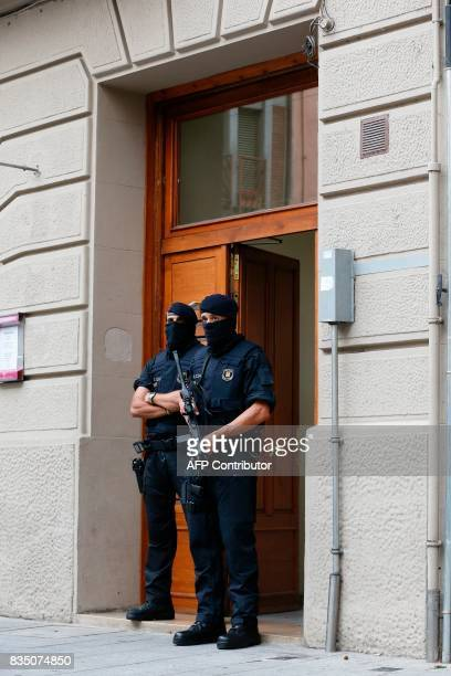 Catalan autonomous police officers known as Mosso d'Esquadra stand guard outside a house in Ripoll during a search linked to the Barcelona and...