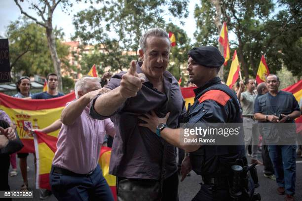 Catalan Autonomus police officer holds an antiseparatist supporter as he argues with Catalan ProIndependence supporters during a demonstration called...