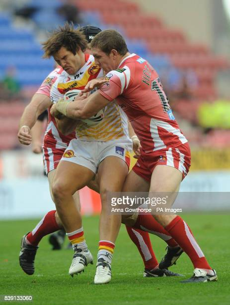 Catalan Dragons Jason Baitiera is tackled by Wigan Warriors Ryan Hoffman and Paul Prescott during the engage Super League match at the DW Stadium...