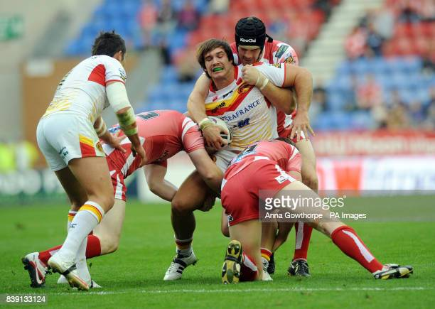 Catalan Dragons Jason Baitiera is tackled by Wigan Warriors Ryan Hoffman Paul Prescott and Liam Farrell during the engage Super League match at the...