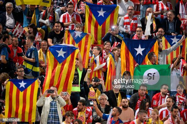 Catalan football fans hold Esteladas and flag reading 'Yes' before the Spanish league football match Girona FC vs FC Barcelona at the Montilivi...