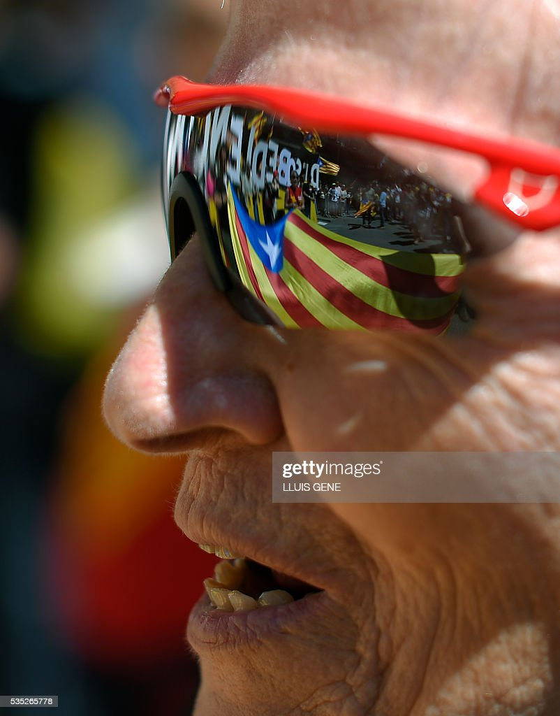 A Catalan independence flag is reflected in the glasses of a protestor during a demonstration called by some 20 social movements, groups and organizations under the slogan, 'Rights, can't be suspended' outside the Catalan government headquarters in Barcelona on May 29, 2016. / AFP / LLUIS