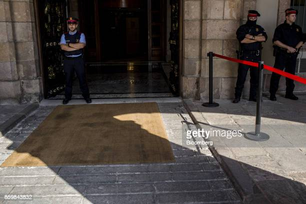 Catalan Mossos d'Esquadra police stand guard ahead of the arrival of Carles Puigdemont Catalonia's president at the entrance to the Catalonian...