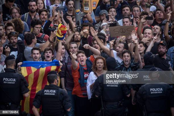 Catalan police officers stand in front of protesters as they gesture at Spanish Police officers in protest of the violence that marred yesterday's...