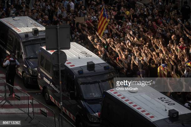Catalan police officers stand in front of protesters as they gesture at Spanish Police officers in protest of the violence that marred yesterdays...