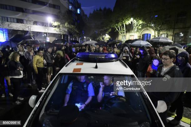 Catalan police sit in their patrol car as people gather outside a polling station in Barcelona on October 1 to prevent the police to seal it off in a...