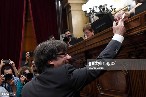 Catalan president Carles Puigdemont casts his vote for a motion on declaring independence from Spain during a session of the Catalan parliament in...