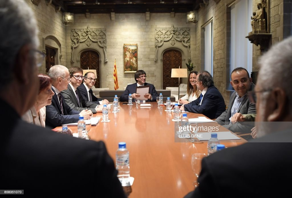 Catalan president Carles Puigdemont (C) holds a meeting with members of the Independent Commission for Mediation, Dialogue and Conciliation at the Catalan Government 'Generalitat' headquarters in Barcelona on October 6, 2017. The Catalan regional government has said it could declare independence next week. It claims voters backed the move in a referendum vote outlawed by Madrid. The political standoff has dragged Spain into its worst political crisis in decades. Catalonia accounts for a fifth of Spain's economy. /
