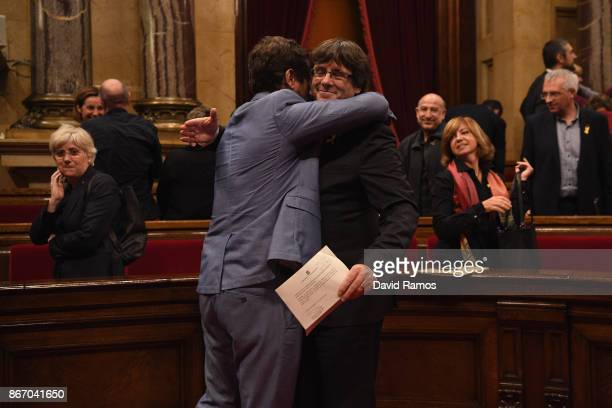 Catalan President Carles Puigdemont is hugged by Minister of Health Antoni Comín as they react to the news that the Catalan Parliament has voted in...