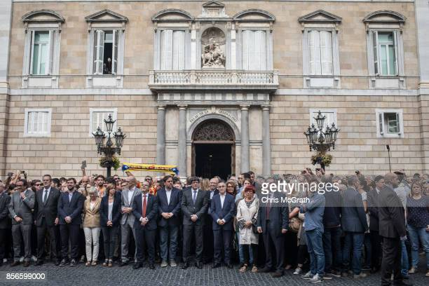 Catalan President Carles Puigdemont joins with government city hall and union officials to pose for photographs in protest of the violence that...