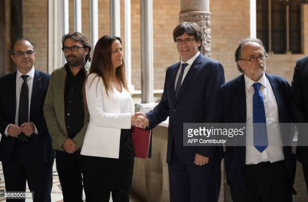 Catalan president Carles Puigdemont shakes hands with the president of the Independent Commission for Mediation Dialogue and Conciliation Maria...