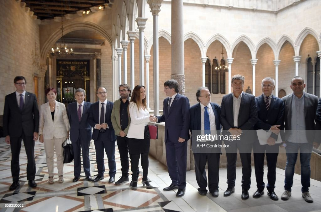 Catalan president Carles Puigdemont (5R) shakes hands with the president of the Independent Commission for Mediation, Dialogue and Conciliation, Maria Eugenia Gay (6R) before holding a meeting at the Catalan Government 'Generalitat' headquarters in Barcelona on October 6, 2017. The Catalan regional government has said it could declare independence next week. It claims voters backed the move in a referendum vote outlawed by Madrid. The political standoff has dragged Spain into its worst political crisis in decades. Catalonia accounts for a fifth of Spain's economy. /