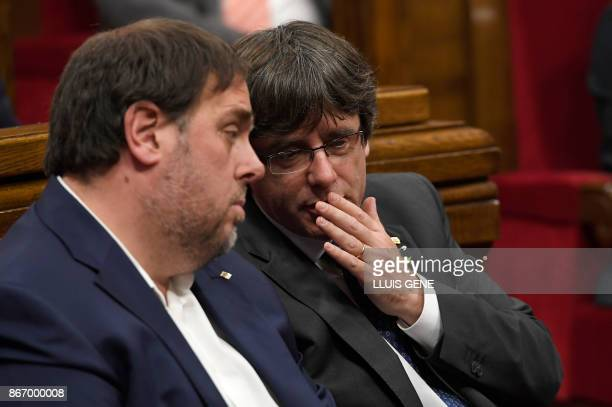 Catalan president Carles Puigdemont talks to Catalan regional vice president and chief of economy and finance Oriol Junqueras during a session of the...