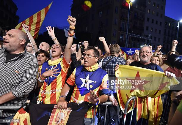 Catalan proindepence supporters raise their arms and wave flags following the closing of polling stations during Catalan regional election on...