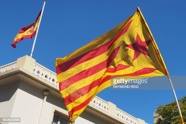 A Catalan proindependence 'estelada' flag is seen next to Spain's national flag atop the Spanish Consulate in Perpignan southern France on September...