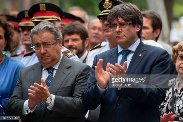 Catalan regional government Carles Puigdemont claps beside Spanish Interior Minister Juan Ignacio Zoido during the ceremony marking the 30th...
