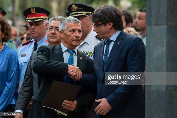 Catalan regional government Carles Puigdemont shakes hands with President of Catalan Association of Terrorism Victims Jose Vargas during the ceremony...
