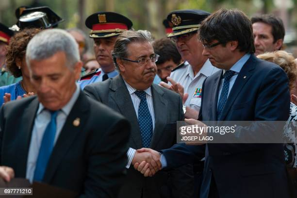 Catalan regional government Carles Puigdemont shakes hands with Spanish Interior Minister Juan Ignacio Zoido during the ceremony marking the 30th...