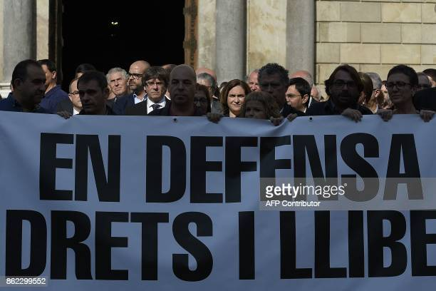Catalan regional government president Carles Puigdemont and Barcelona mayor Ada Colau stand with other officials holding a banner reading 'In defence...