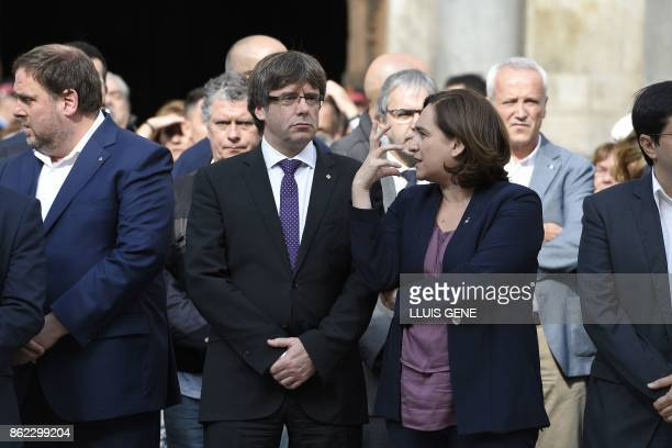 Catalan regional government president Carles Puigdemont speaks to Barcelona mayor Ada Colau as they stand with other officials during a protest...