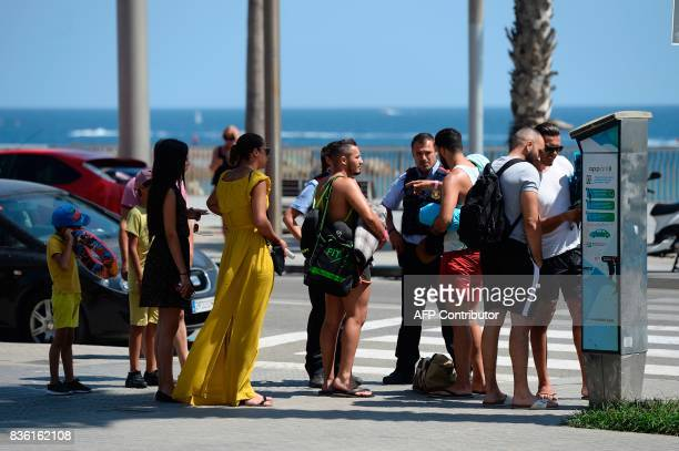 A Catalan regional police 'Mossos D'Esquadra' member speaks with tourists on a pedestrian street next to a beach of Barcelona on August 21 2017 four...