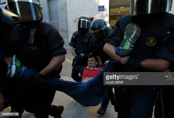 Catalan regional police officers 'Mossos D'Esquadra' drag a man during a protest against a search for propaganda supporting Catalonia's independence...