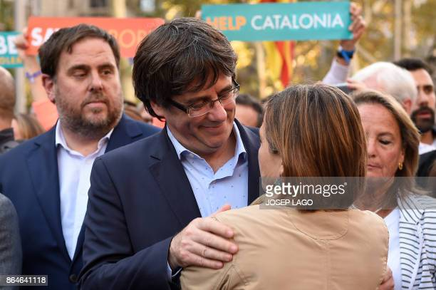 Catalan regional president Carles Puigdemont greets president of the Catalan parliament Carme Forcadell during a demonstration on October 21 2017 in...