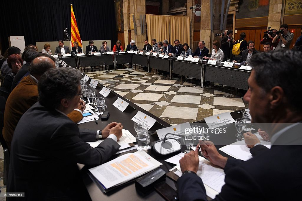 Catalan regional president Carles Puigdemont (far 4thL) presides the political and social summit in defense of the law of social emergency appeal by the Spanish Government with representatives of institutions, political and civil entities of Catalonia in Barcelona, on May 3, 2016. / AFP / LLUIS