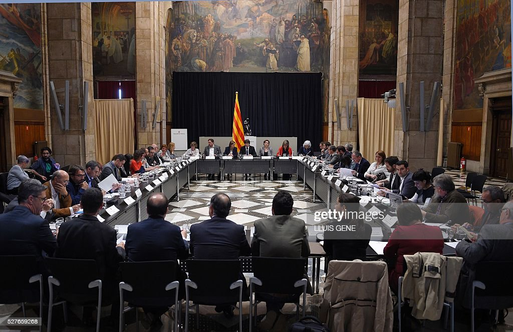Catalan regional president Carles Puigdemont (far C) presides the political and social summit in defense of the law of social emergency appeal by the Spanish Government with representatives of institutions, political and civil entities of Catalonia in Barcelona, on May 3, 2016. / AFP / LLUIS