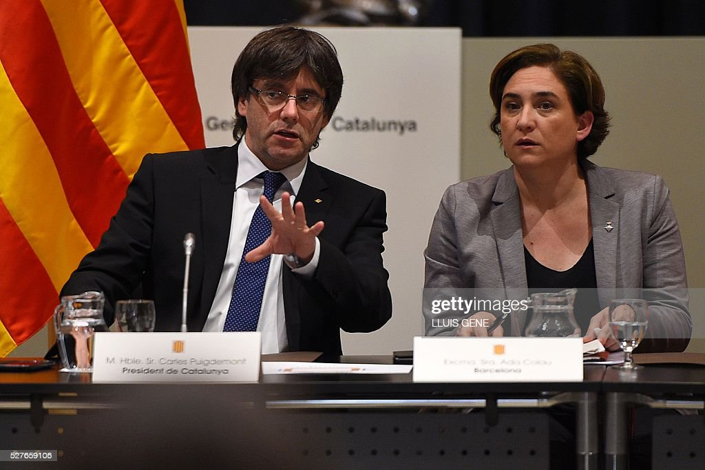 Catalan regional president Carles Puigdemont (L) talks with the Barcelona's mayor Ada Colau during the political and social summit in defense of the law of social emergency appeal by the Spanish Government with representatives of institutions, political and civil entities of Catalonia in Barcelona, on May 3, 2016. / AFP / LLUIS