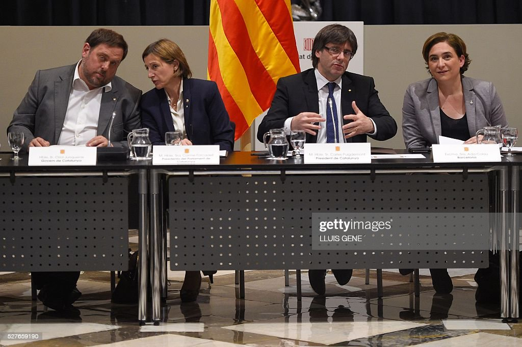 Catalan regional vice-President and chief of Economy and Finance Oriol Junqueras, Catalan Parliament President Carme Forcadell, Catalan regional president Carles Puigdemont and Barcelona's mayor Ada Colau talk during the political and social summit in defense of the law of social emergency appeal by the Spanish Government with representatives of institutions, political and civil entities of Catalonia in Barcelona, on May 3, 2016. / AFP / LLUIS