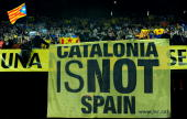 Catalans hold a large banner reading 'Catalonia is not Spain' as the Catalan anthem played prior to the start of the international friendly match...