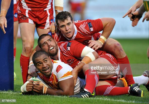 Catalans' Lopini Paea scores a try despite being held by Salford's Lee Jewitt and Matty Ashurst
