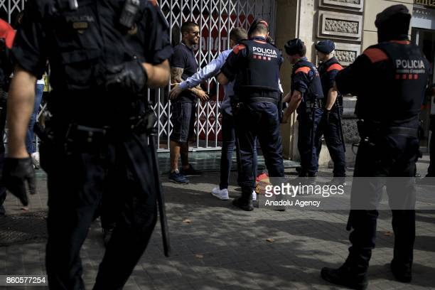 Catalonian autonomous police officers body search a far right supporter after a demonstration supporting Spain unity on October 12 2017 in Barcelona...